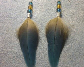 Blue macaw feather earrings adorned with blue and yellow Czech glass beads.