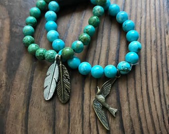 Set of two elasticated charm bracelets. Turquoise howlite , bird and two tone feather charms