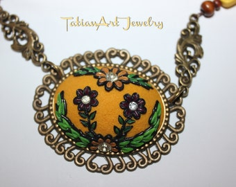 Cameo necklace bronze tones. Flower watermark in polymer clay.
