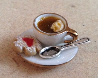 Miniature cup of coffee with biscuit and spoon, dollhouse