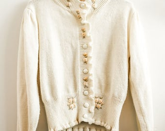 Cream coloured cardigan with embroidered flowers.