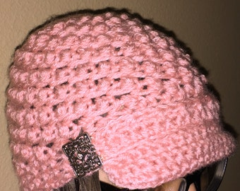 Soft pink colored hat...has bill with 2 deceptive square metal buttons on each side