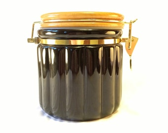 Black canister with wooden lid and gold locking mechanism