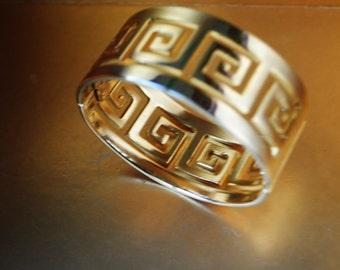 Classy vintage 80s, light gold tone metal,  wide cuff, hinged bracelet with a greek key pattern.