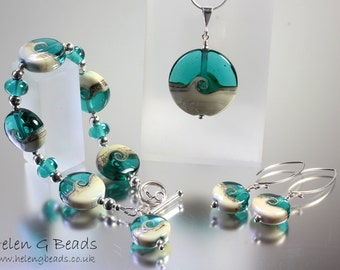 Jewellery set in teal cream. Includes 1 bracelet, 1 pendant on a chain and 1 pair of earrings.
