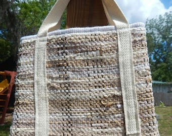 Tan and white handwoven handbag with a tan hande and cream and white fabric liner