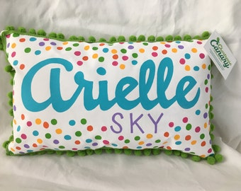 Pillow with rainbow polka dots and name in bright purple and turquoise.