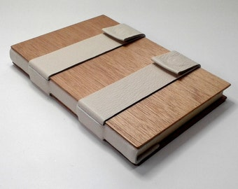 Blank book, bound in wood, white cream pale leather, cream-color lined pages, closes with magnetic snaps.
