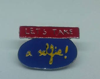 A large 'Let's Take a Selfie' enamel brooch pin