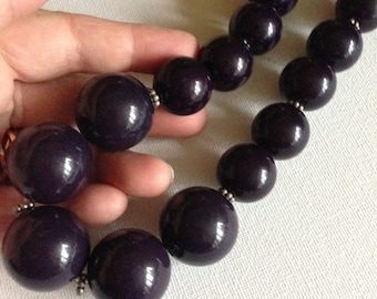Necklace - plastic beaded necklace with large deep purple beads smaller around the neck