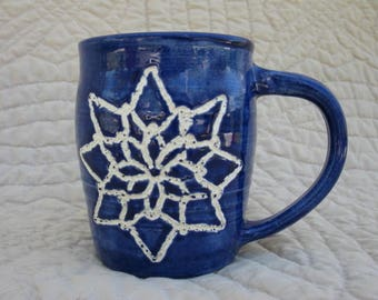 Snowflakes in blue pottery mug