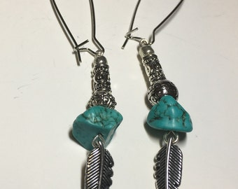 Earrings with turquoise and silver beads and feathers.