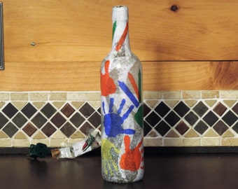 Kids' hands and crayons tissue paper collage on recycled wine bottle