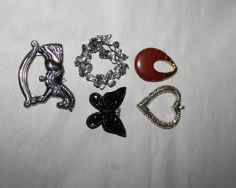 Supplies for Making Jewelry Pendants including a Horse, Butterfly, Heart and an Oval which is a dark red.  There is also a round pendant