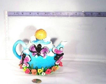 Ceramic teapot decorated with Fimo / Polymer clay flowers & butterflies. A bright, sunny garden scene.