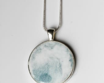 Partly cloudy skies in this blue and white resin pendant!