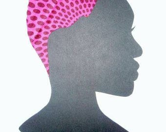 Female silhouette in pink African print fabric cut paper art