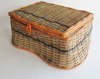 Vintage wicker sewing basket with orange plastic trim, gold padded lid and lining.