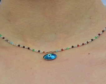 RAS's neck with an eye pendant and a string with multi-colored beads