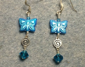 Dark turquoise metallic Czech glass butterfly bead dangle earrings adorned with silver swirly connectors and turquoise Saturn beads.