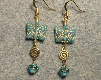 Aqua Czech glass butterfly bead dangle earrings adorned with gold swirly connectors and aqua Czech glass Saturn beads.