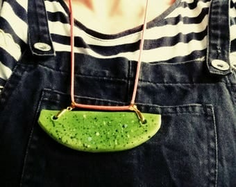 Modern one of a kind handmade ceramic mottled spotty green necklace on pink cord. Yum!
