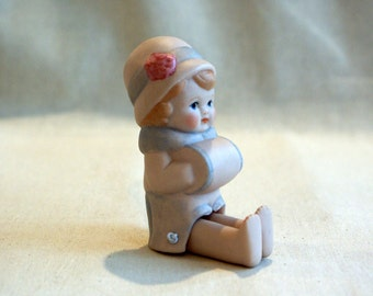 Cute miniature porcelain doll with winter muff and cloche hat