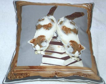 very pretty ginger and white kittens  climbing down a mountain of books cushion !