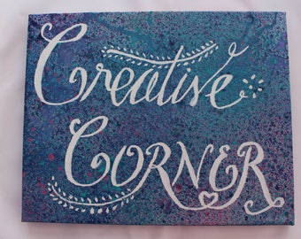 Creative Corner Canvas for your creative space.  White hand lettering on Blue/sea green, with pink splattered background. 10 x 8 inches