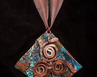 Rustic fold formed copper patina pendant with blue patina and copper wire triskele and hand dyed silk ribbon