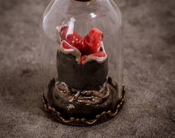 Trailer alien egg under a glass Bell with leather strap