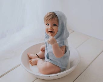 Baby Boy Newborn/Sitter In a baby blue stretch soft feel warm fabric.With a self tie at the neck.Hooded & sleeveless and short legs Cute