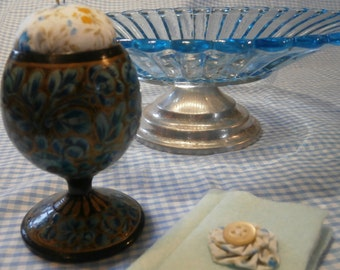 Vintage wooden egg cup repurposed into a pincushion with needlecase
