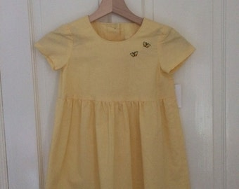 Yellow cotton sundress with appliqué butterflies and three button opening at back. Age 4years.