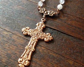 Ornate copper cross necklace on a rose quartz rosary chain.