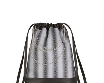 Leather backpack with optical illusion textile design print