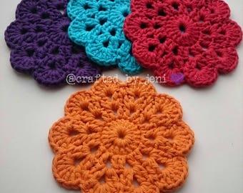 100% cotton crocheted flower drinks coasters/mats x4. Handmade. Protection. Multi-coloured. Orange. Red. Blue. Purple. 12cm-13cm diameter.