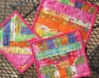Pot holders and hot pad, set of three pieces. Scrappy, quilted, washable, and reversible.