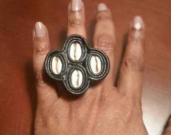 Recycled leather and quadruple cowrie shell adjustable ring.