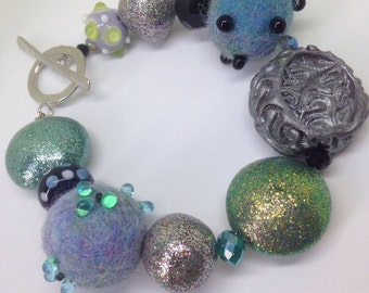 A bracelet in soft blues and greens. Beaded felt and polymer.