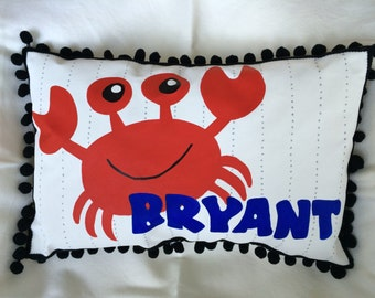 Pillow with bright red crab and name in dark blue