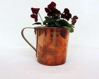 A vintage Nigerian, Maggie, copper measuring cup with tin lining and copper handle