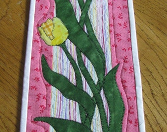Springtime is coming!  This handmade, quilted and appliquéd small wall hanging has tulips springing up!
