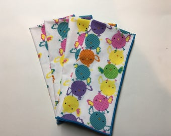 Set of 4 Easter cloth dinner napkins with Multi Colored Chicks on a white background.