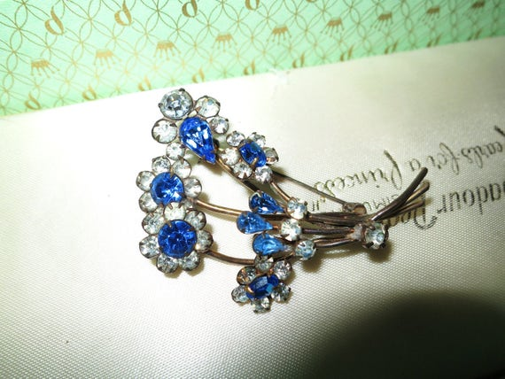 Wonderful 1950s gold metal brooch with clear and blue rhinestones in a flower design