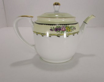 Vintage Noritake teapot with lid cream with a band of flowers on top quarter of the pot rimmed in gold
