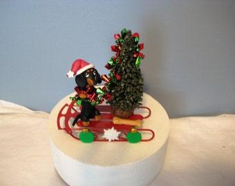 Clay dachshund dog on a sled decorating a Christmas tree, sculpture, handmade, OOAK, whimsical, keepsake, decor, holiday