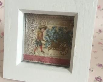 Mixed media vintage boy with wheelbarrow of flowers framed art