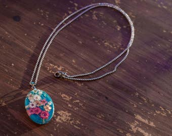 clear resin charm necklace, blue background colored flowers