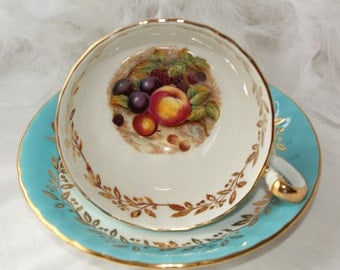 Aynsley, England: turquoise set, signed D. Jones footed tea cup with saucer, orchard fruit pattern